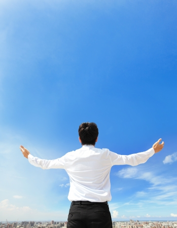 back view of business man arms up and looking to empty copy space isolated on blue sky background, asian model photo