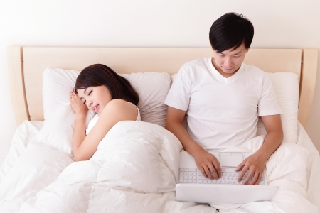 Cheerful couple using touch pad and computer in bed at home, asian people photo