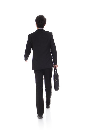 full suit: back view of a business man holding a briefcase and walking forward onwhite background