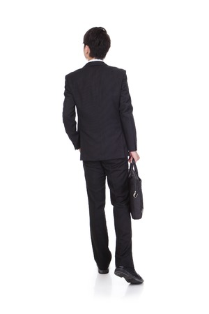 back view of a business man holding a briefcase and walking forward onwhite background
