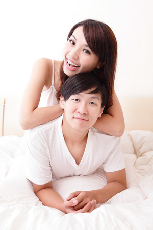 young lovely couple lying in a bed, happy smile looking to camera, asian people photo