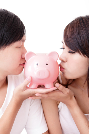 young happy couple kiss pink piggy bank, asian family photo