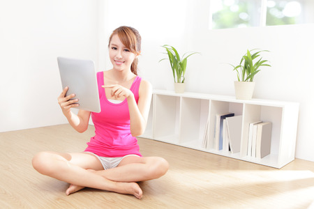 happy woman smiles using tablet pc at home, asian beauty model Stock Photo - 22350708