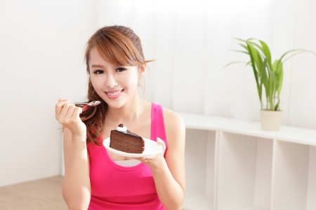chinese: beautiful happy woman smiles eating chocolate cake at home, asian beauty model