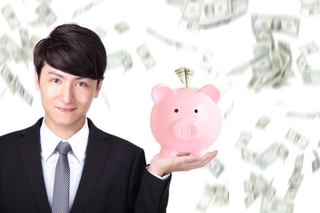 Attractive business man holding pink piggy bank with money falling background, asian model photo