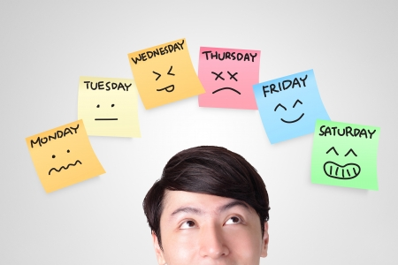 closeup of young man looking up with color stickers displaying day of week and face expression on each separate color, asian man Stock Photo - 22449099