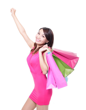 to raise: happy shopping young woman raise arms with bags - isolated on white background, asian model