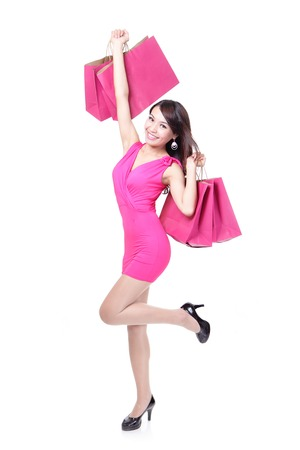 happy shopping young woman running with color bags - isolated on white background, full body, asian model photo