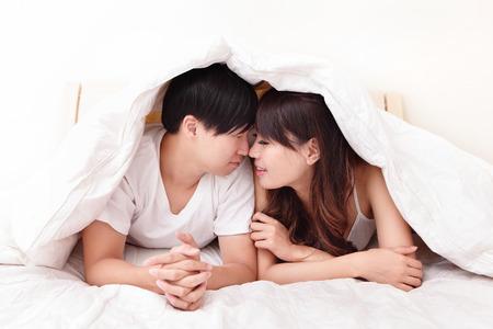pareja en la cama: encantadora pareja joven acostado en una cama, cara de la sonrisa feliz, gente asi�tica