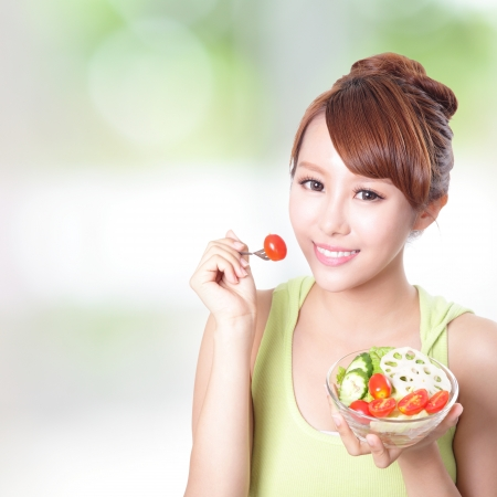 portrait of attractive woman smile eating salad isolated on green background, asian beauty model Stock Photo