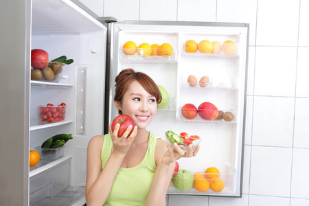 icebox: Healthy Eating Concept .Diet. Beautiful Young Woman hold apple near the Refrigerator with healthy food. Fruits and Vegetables, asian model