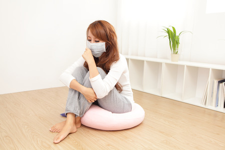 respirator: Sick Woman caught Cold and cough at home. asian female