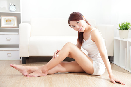 Beauty of young pretty woman with perfect shape and applying cream on her attractive legs indoors at home, asian beauty photo