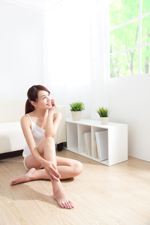 woman sitting floor: Beautiful skin care young woman happy hand touch her skin of face at home, asian beauty