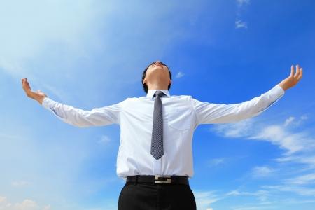 青空の背景、アジアのモデル上で分離されて屈託のないビジネスの男の腕を空のコピー スペースを探して