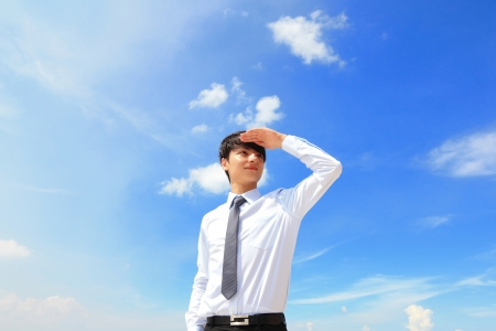 Successful handsome business man purposefully looking away with blue sky, mode is a asian male photo