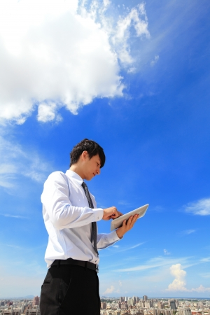 Young business man using tablet pc with cityscape and cloud in the background, business and cloud computing concept photo