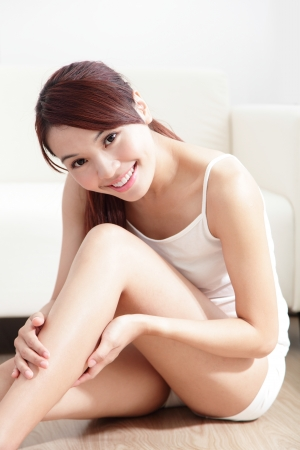 moisturizing: Beauty of young pretty woman with perfect shape and applying cream on her attractive legs indoors at home, asian beauty