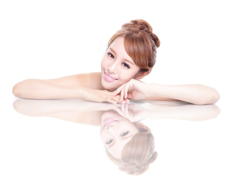 Beautiful face skincare beauty woman lying down with mirror reflection isolated on white background. asian beauty model Stock Photo - 22578443