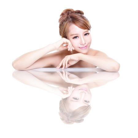 Beautiful face skincare beauty woman lying down with mirror reflection isolated on white background. asian beauty model Stock Photo