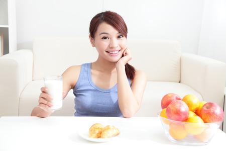 Vrolijke vrouw consumptiemelk zittend op haar sofa thuis, Aziatische schoonheid