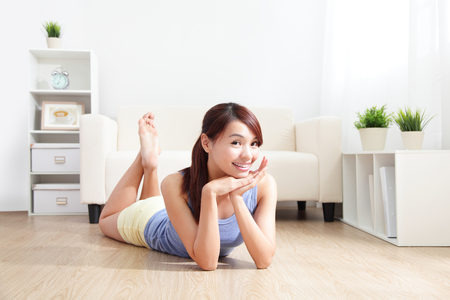 Smiling young woman  lying on floor with her couch at home, asian beauty Stock Photo - 22851671