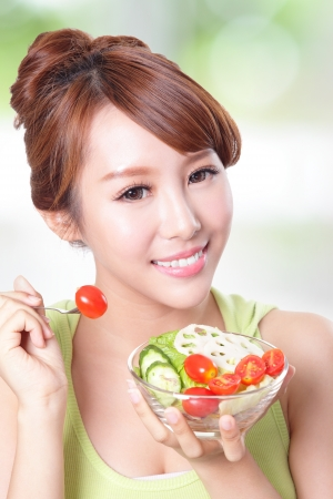 beautiful salad: portrait of attractive woman smile eating salad isolated on green background, asian beauty model Stock Photo