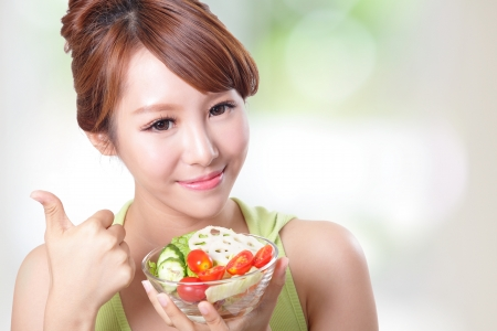 portrait of attractive woman smile eating salad isolated on green background, asian beauty model photo