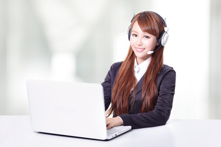 Friendly call center secretary consultant woman with headset telephone and pretty smile in office, asian model photo