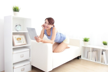 happy woman using tablet pc on sofa in the living room, asian beauty Stock Photo - 22673806
