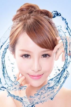 rosto humano: Retrato bonito da mulher com pele fresca em salpicos de água, conceito de beleza do cuidado da pele isolada no fundo azul, modelo asiático