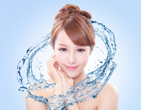 Beautiful portrait of woman with fresh skin in splashes of water , concept for beauty skin care isolated on blue background, asian model Imagens