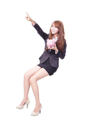 Happy business woman holding pink piggy bank and sitting on something isolated against white , asian male model photo
