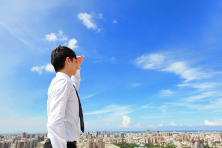 Successful handsome business man purposefully looking away with blue sky and city background, mode is a asian male photo
