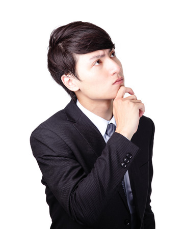 Closeup of a handsome young business man thinking against white background, asian male photo
