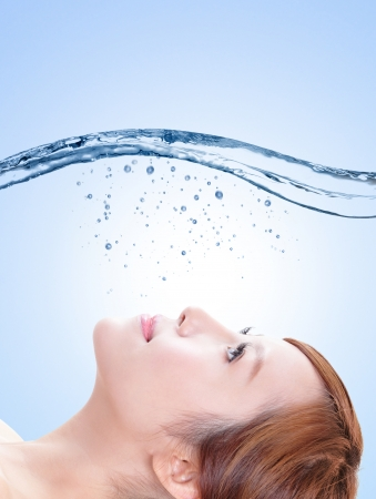 care for: Beautiful portrait of woman with fresh skin in splashes of water , concept for beauty skin care isolated on blue background, asian model Stock Photo