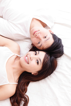 young lovely couple lying in a bed, happy smile together, top view, asian people photo