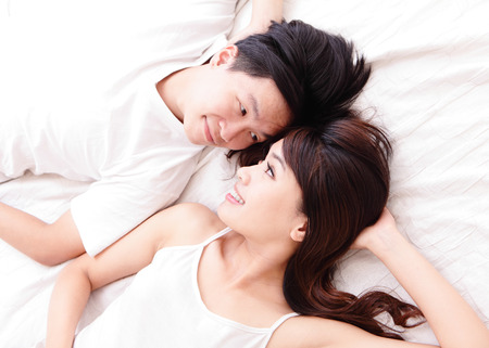 young lovely couple lying in a bed, happy smile looking to each other, top view, asian people photo