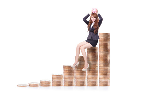 Happy business woman holding pink piggy bank and sitting on money stairs isolated against white background, business concept photo