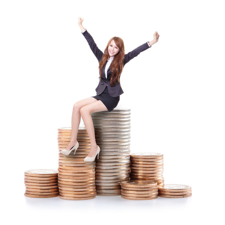 winning stock: Excited business woman sitting on money and raise arms isolated against white background, business concept