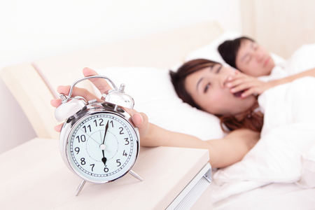 Wake up - Tired couple touch the alarm clock while they are sleeping in bed, asian family photo