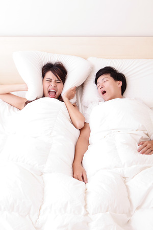 Young woman disturbed by the snores of her husband in the bedroom at home, asian family photo