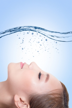 splashing water: Beautiful portrait of woman with fresh skin in splashes of water , concept for beauty skin care isolated on blue background, asian model Stock Photo