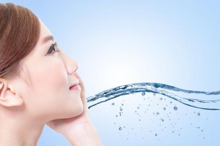 Mooi portret van vrouw met frisse huid in waterspatten, concept voor schoonheid huidverzorging geïsoleerd op een blauwe achtergrond, Aziatische model