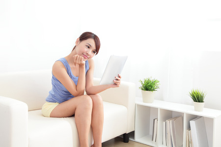 happy woman using tablet pc on sofa in the living room at home, asian beauty Stock Photo - 22886554