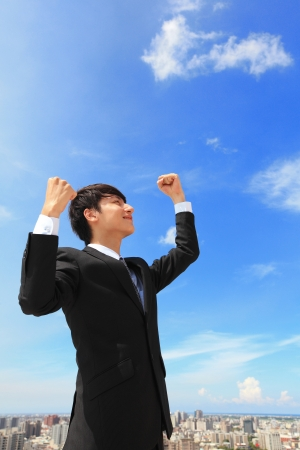 emotional freedom: happy successful business man raised arms with sky in the background, asian people