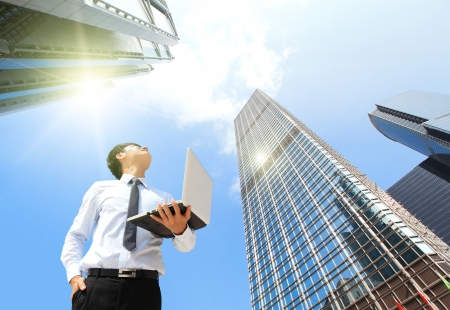 economy: Young business man using laptop and look to blue sky and cloud with cityscape, hong kong, asia, business and cloud computing concept Stock Photo