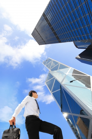 peak: happy successful business man outdoors Next to Office Buildings with cityscape and sky, hong kong, asia, , asian people