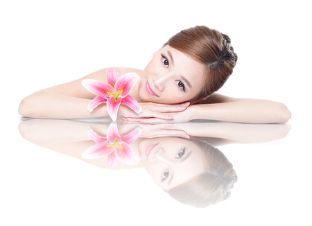 Beautiful face skincare beauty woman lying down with pink lily flower amd mirror reflection isolated on white background. asian beauty model