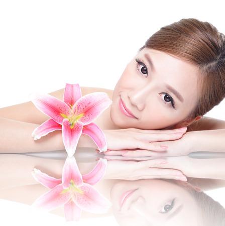 Beau visage soins beauté de la femme couchée avec lis rose réflexion fleur de miroir d'amd isolé sur fond blanc. modèle de beauté asiatique